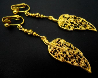 A pair of pretty gold colour long dangly leaf themed clip on earrings.
