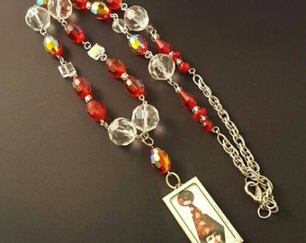"""A charmed life red and clear glass bead """"Y"""" necklace with a collaged clown pendant"""