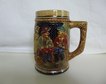 "Small beer stein with raised relief images, marked ""Foreign"""