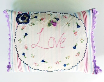 Handmade cushion using vintage embroideries, applique and crochet with feather inner