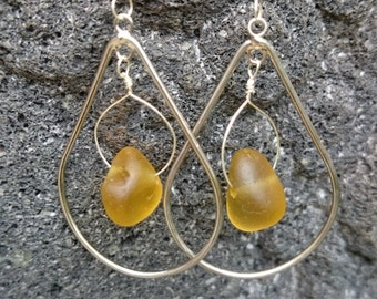 Golden yellow seaglass hung from hand formed sterling silver hoops inside silver teardrops