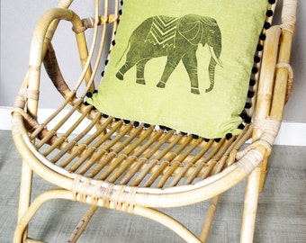 Green cushion with elephant pattern and pompoms