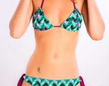Conxita No.386 Geometric zigzag print in shades of green, pink and black. Top straps and tie sides in wine red, trim in aquamarine.