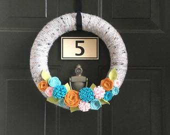 Gray spring yarn wreath with turquoise, pink and yellow flowers