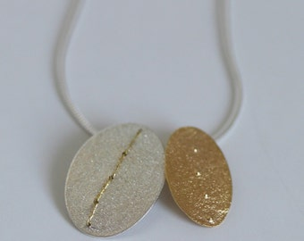 Silver and gold plated oval discs pendant stitched with embroidery thread