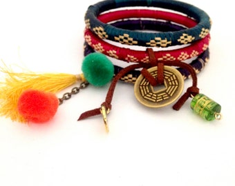 A set of three stacked raffia charm bangles with tassels. Bohemian stacked bangles, colorful charm bangles, tassel bangles