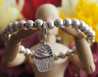 An adorable cupcake charm handmade from fine silver on a sterling silver bead bracelet ....