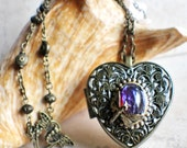 Music box locket, heart shaped locket with music box inside, in bronze with a dragons breath glass fire opal, and dragonfly.