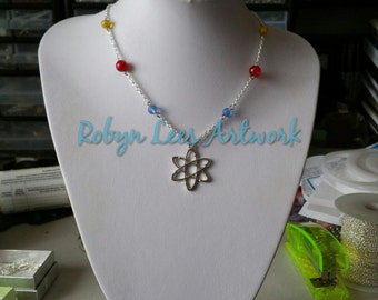 Silver Atom Molecule Necklace with Blue, Yellow and Red Beads on Silver Crossed Chain. Proton, Neutron, Electron. Science, Chemistry