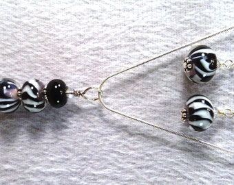 Handmade flamework bead. earrings and pendent set in black and white