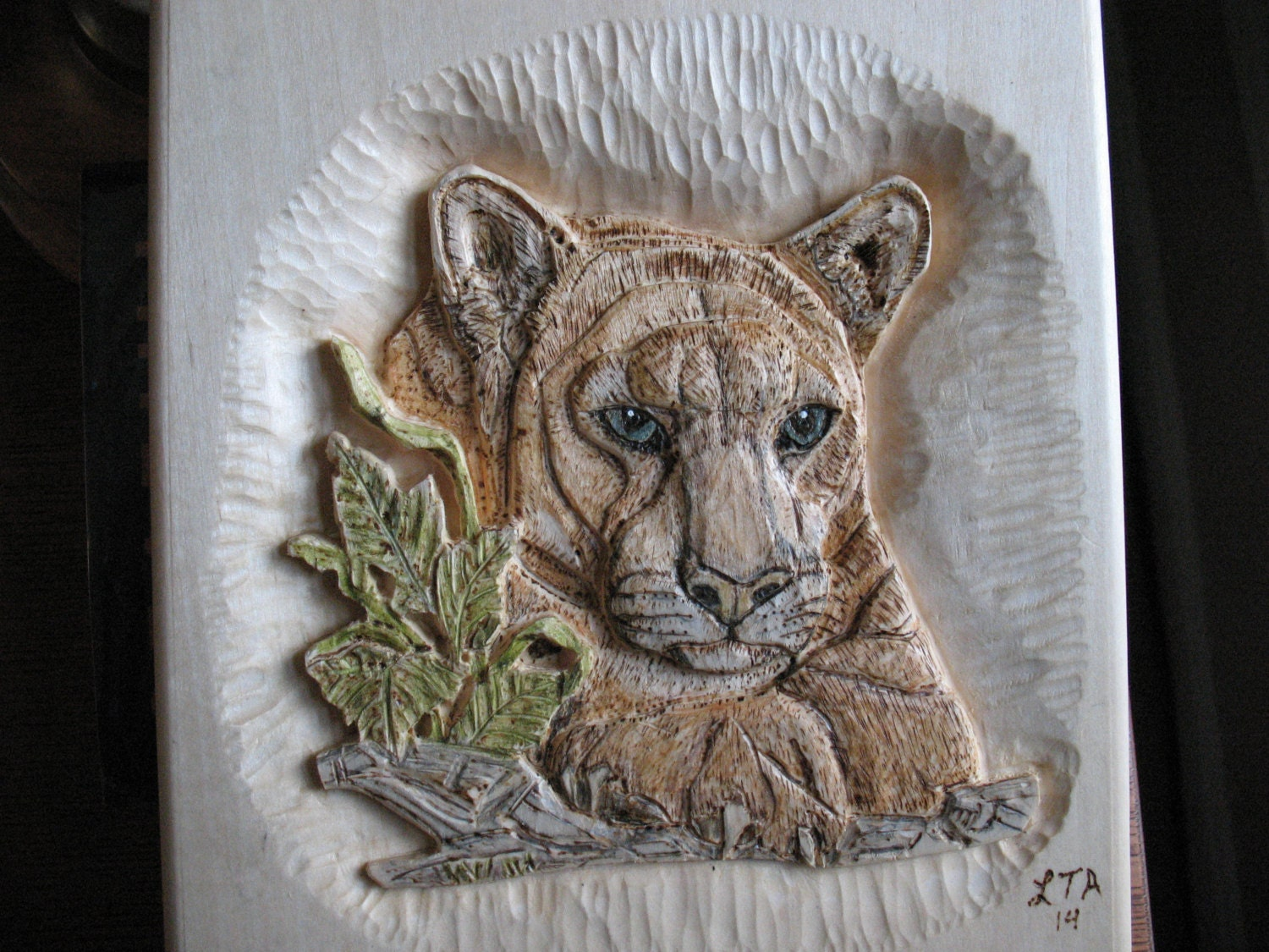 Relief carving of a mountain lion portrait