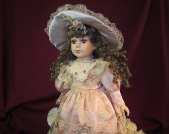 """Emerald Doll Collection """"Marilyn"""" 18"""" porcelain doll on stand with hat,purse,shoes,under clothes,peachy color lacey dress,brown eyes & hair"""
