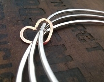 Three Silver bangles with rose gold heart
