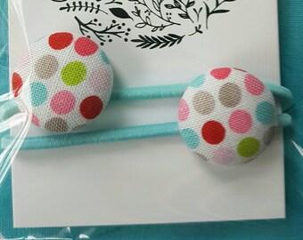 Cute fabric covered button hair elastics.