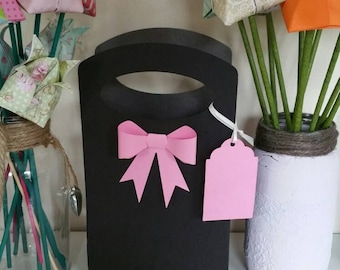 Black card gift bag with pink 3D bow and tag.