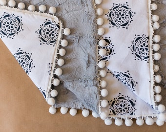 Baby girl crib blanket with pom pom trim - Navy and white medallions with silver hide minky back