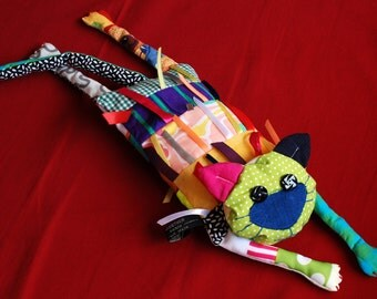 "Cat ""Teddy"" in colourful fabrics strewn with colorful ribbons"