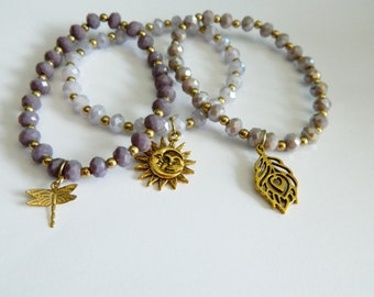 Set of 3 pastel stretch bracelets with antique gold tone charms