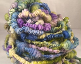 Handspun beehives and coils yarn with blues, purples and greens with a touch of natural white