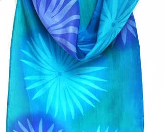 Blue and purple spring flowers painted on a silk scarf. The vibrantly coloured scarf is a one of a kind handmade item using batik technique