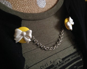 white bows on yellow sweater clip