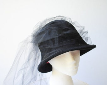 Glamour vintage 80s black velvet, cloche style with  hat with a flower on the back and long tull vail. Made by Frank Olive.Size 21.