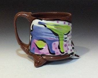 Mug with purple and green on a splash of white. Handmade terra cotta mug