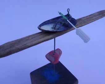 SHeLL CaNoE: Recycled sculpture with miniature canoe/figure.