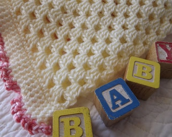 Crocheted Baby Blanket in a Soft Shade of Creamy Yellow with a Fancy Pink Edge
