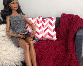 Delicate handknit throw blanket in burgundy with matching pillows in coral for sixth scale or playscale diorama or dollhouse