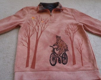 Our adorable bear is riding his bike, wishing upon the first two stars of the night, man's small outerwear, discharged and screen printed