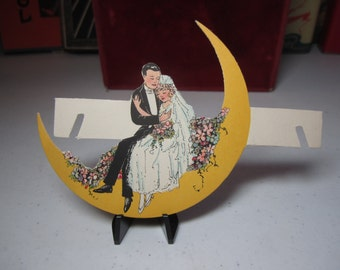 Gorgeous unused art deco die cut fantasy wedding place card 1920's bridge and groom sitting inside yellow crescent moon