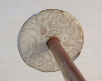 Ceramic whorl on a cherry shaft.