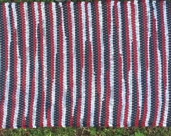 Hand woven rag rug in maroon, white, and black
