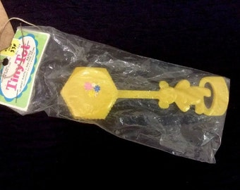 Vintage Tiny Tot Rattle. NIP. Yellow With Lowers. Plastic.