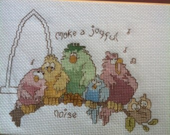 A Completed Framed Cross Stitch That Reads Make A Joyful Noise