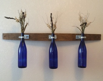 Wine bottle bud vases on wine barrel stave