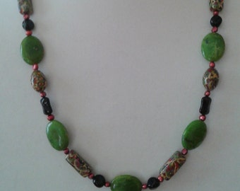 Unique beads and design in this one of a kind necklace. Multi shaped beads, fresh water pearls in maroon, greens, and black has copper clasp