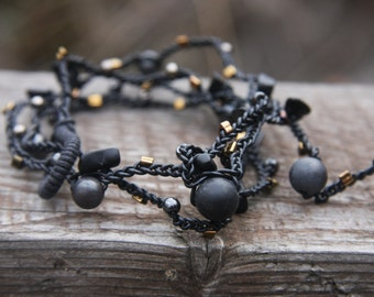 Black beaded bracelet, braided with rubber cord and glass beads