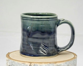 Made to order, ergonomic handmade in the USA 8-12oz clay coffee/tea/cordial mug. Food, dishwasher, and microwave safe.