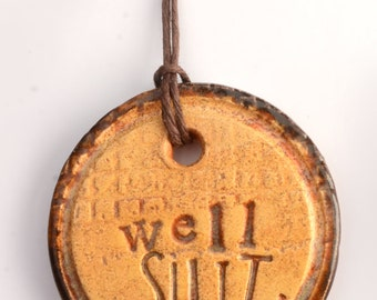 small ceramic pendant necklace with cursing and burgandy rim