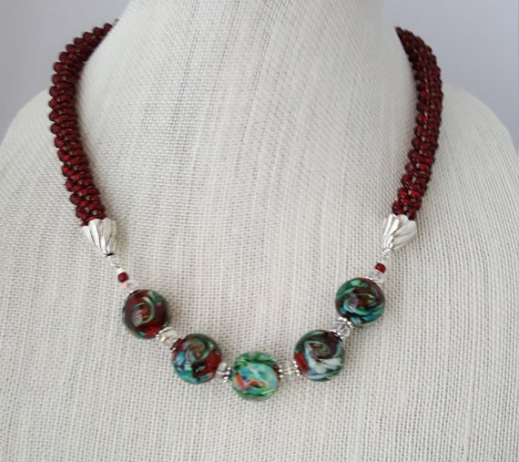 Red beaded kumihimo woven necklace with red and green swirled glass marble beads