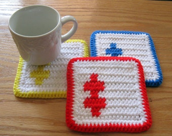 Puzzle Coasters. Set of 3, white crochet coasters with primary color puzzle pieces. Red, yellow, blue coaster set