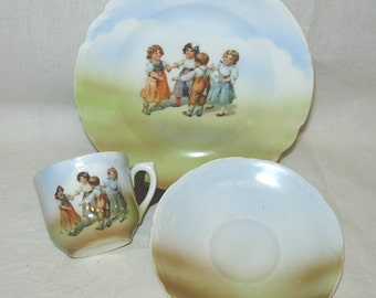 German Porcelain Child's Cup-Saucer-Plate Set HP Children Playing Ring Around the Rosie Germany