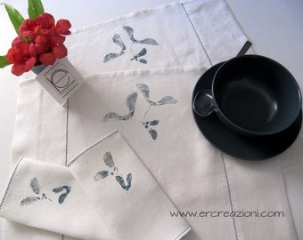 Place mats in white linen, hand-printed and embroidered.