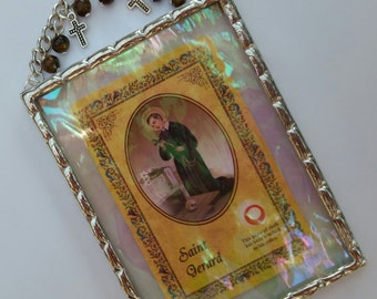 Saint Gerard plaque with a third class relic and tigers eye beads along with tiny crosses soldered in iridescent water glass