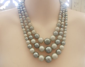 1950s 3 strand graduated bead necklace in two shades of grey will set off a vintage 1950s outfit.