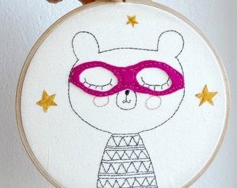 Broderie encadrée/ Décoration murale/ illustration originale/Petit ours super-héros rose /19 cm diamètre/ Prêt à partir/ Pièce unique