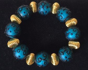 Blue And Black Embossed Bracelet With Gold Stations