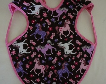Child's pony bib that covers a large part of their body.  Reversible with cotton on one side and flannel on the other.